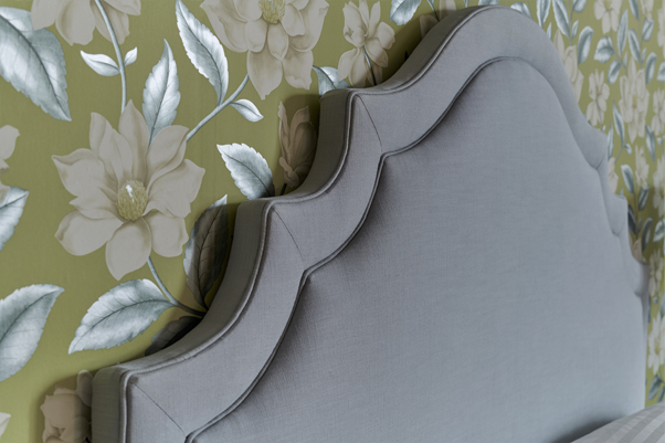 Ornate Curved Shape with Border and Buttons Bardsey Headboard upholstered in Pure Cotton Ice Blue Fabric with Self Piping and No Buttons in a Jardin Des Plantes Green and White Floral Wallpapered Room