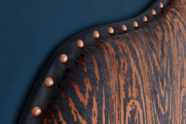 Pointed Teardrop Curved Style Ewe Headboard upholstered in Kai Marva Copper with a Frame Border in Flat Velvet Anthracite with Giant Copper Nails in a Farrow & Ball Hague Blue painted room