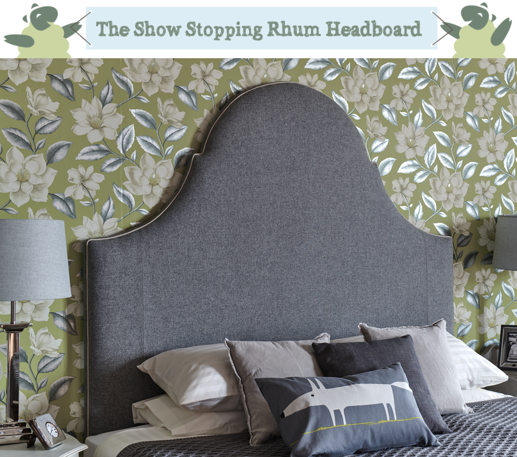 Tall Curved Period Style Rhum Headboard upholstered in Wool Plain Mid Grey and Contrast Piped in Pure Cotton Natural in a green floral wallpapered room